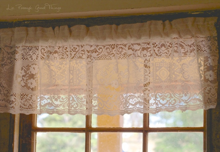 Lacy curtains look out to the garden at Cooma Cottage